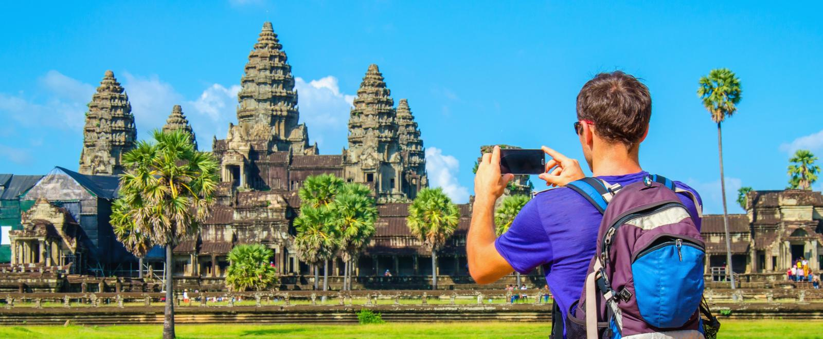 Traveller takes a photo of Angkor Wat during his Discovery Tour in Cambodia.